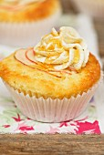 An apple cupcake decorated with buttercream and maple syrup