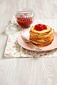 A stack of pancakes with strawberry jam