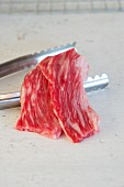 Wagyu and a pair of metal tongs