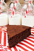 Slice of chocolate cake in front of bottles of milk
