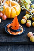 A Halloween hat in front of ornamental pumpkins and apples