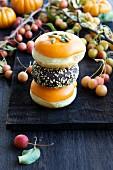 Verschiedene Donuts zu Halloween mit Zierkürbissen und Zieräpfeln