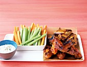 Glazed chicken wings with celery and carrot sticks and a blue-cheese dip
