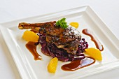 Duck leg with orange and red cabbage