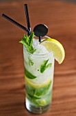 A mojito with mint, ice cubes and lemon