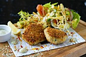 Salmon cakes with a mixed leaf salad and tartare sauce