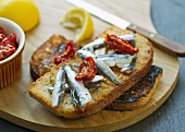 A slice of toast topped with smoked anchovies and dried tomatoes