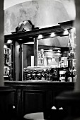 The interior of an Italian bar with a mirror and an espresso machine