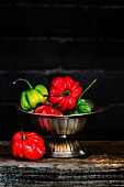 Red and green Scotch Bonnet chillis in a metal bowl