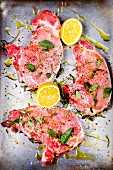 Raw pork chops marinated in olive oil, sage, lemon juice, salt and pepper
