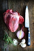 A pig's heart on a wooden board with an old knife, onions, garlic, thyme and salt
