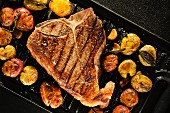 Porterhouse steak with roast potatoes in pan