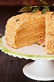 A sliced honey cake on a cake stand
