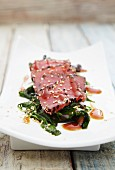 Tuna sashimi with sesame seeds on a bed of spinach
