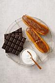 Eclairs mit Schokoladenglasur, Schokoladentafel und Zucker auf Kuchengitter