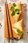 Samosas, fresh mint and chopsticks on a wooden board