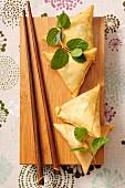 Samosas, frische Minze und Essstäbchen auf Holzbrett
