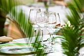 Weingläser und Teller auf gedecktem Tisch in elegantem Restaurant (Frankreich)
