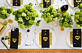Festively set table decorated with hydrangeas & cutlery in bags