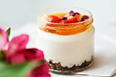 White chocolate cream with caramel and strawberries in a screw top jar