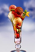 An ice cream sundae with fresh fruits against a cloudy sky