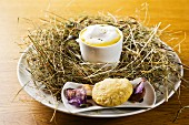 A cup of pumpkin foam soup with poppyseed oil in a nest of hay