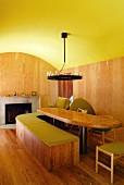 Gelbgrün getünchte Tonnendecke in Raum mit Esstafel und gebogener Sitzbank aus Holz vor modernem offenem Kamin