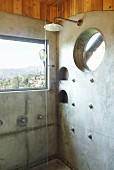 Dusche vor Fenster mit Ausblick in Badezimmerecke mit teilweise betonierter Wand und eingelassenen runden Ablagen