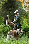 Mann mit Hund bei der Gartenarbeit