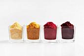 Vier verschiedene Fruchtpulver in Gläschen