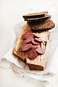 Elk salami and black bread on a wooden board (Estonia)