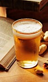 A glass of beer and peanuts next to an open book