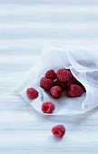 Fresh raspberries on a piece of white fabric