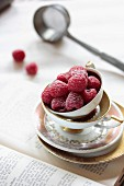 Raspberries dusted with icing sugar in an old-fashioned teacup