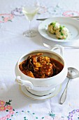 Pork goulash in a terrine with a plate of bread dumplings in the background