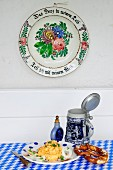 Obatzda (Barbarian cheese spread) with a pretzel, a tankard and a snuff bottle underneath an old fashioned painted plate hanging on a wall