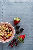 A bowl of muesli next to fresh berries