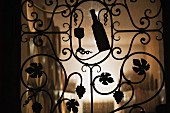 A wrought iron gate leading to a wine cellar