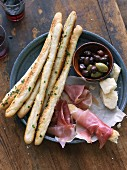 An appetiser platter with breadsticks, ham, cheese and olives