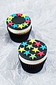 Two lemon cupcakes decorated with stars