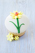 A cupcake decorated with icing sugar and daffodil for St David's Day (Wales)