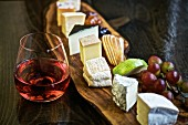 A mixed cheese platter with fruit and red wine