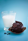 A chocolate cupcake and a glass of milk
