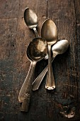 Old silver spoons on a wooden table