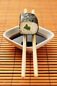 Maki sushi with cucumber balanced on chopsticks over a dish of soy sauce