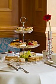 Biscuits, sweet pastries and sandwiches on a cake stand for high tea (England)