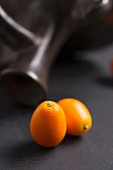 Two kumquats in front of a terracotta jug