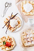 Belgian waffles served with ice cream, strawberries, whipped cream and vanilla pods