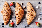 Three croissants with blueberries, strawberries and sugar cubes