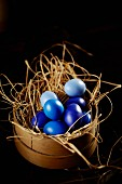 Blue Easter eggs in straw in a woodchip basket